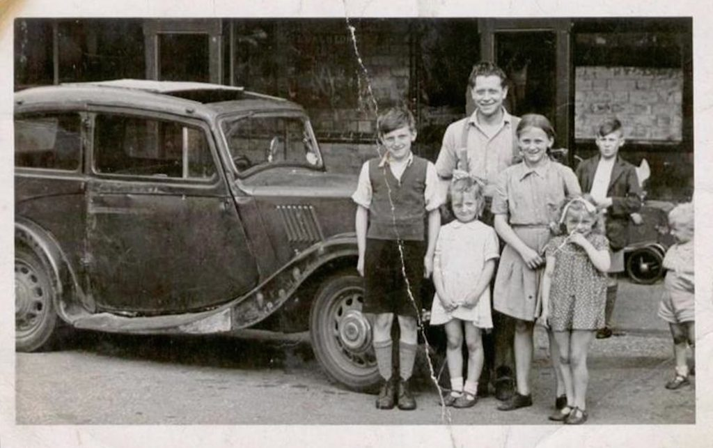 Joe Junior, Joe, Josie and Shirley outside the Refreshment Rooms standing next to the car Joe purchased with his testimonial money from Stoke City.